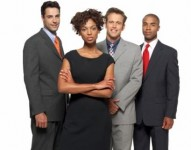 Front view portrait of three mid adult businessmen and mid adult businesswoman